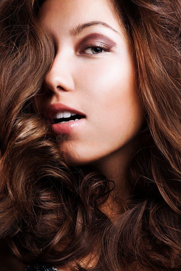 Schöne junge Frau mit den langen gelockten Haaren lizenzfreie stockfotos