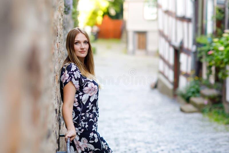 Schöne junge Frau mit den langen Haaren im Sommerkleid, das in der deutschen Stadt spazierengeht Glückliches Mädchen, das herein  stockfoto