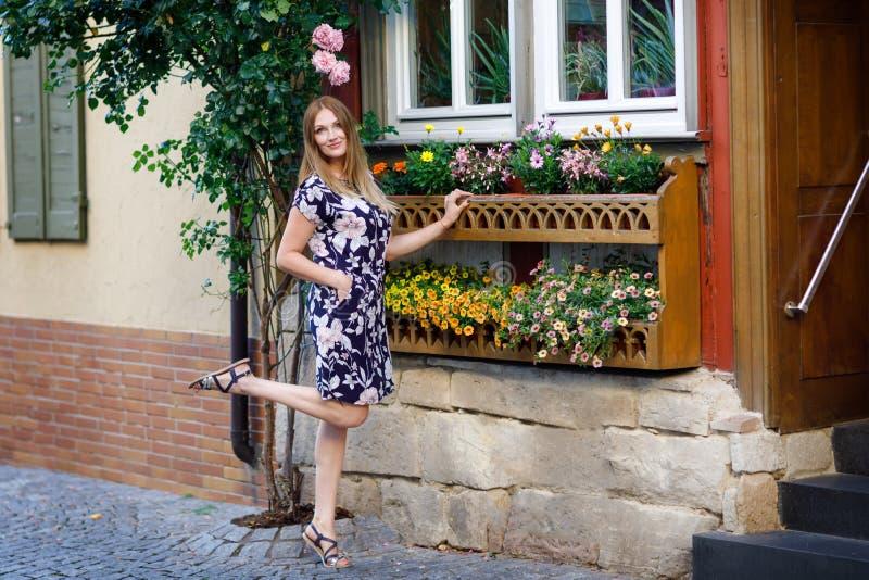 Schöne junge Frau mit den langen Haaren im Sommerkleid, das in der deutschen Stadt spazierengeht Glückliches Mädchen, das herein  lizenzfreies stockfoto