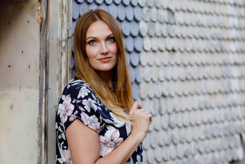 Schöne junge Frau mit den langen Haaren im Sommerkleid, das in der deutschen Stadt spazierengeht Glückliches Mädchen, das herein  stockbild