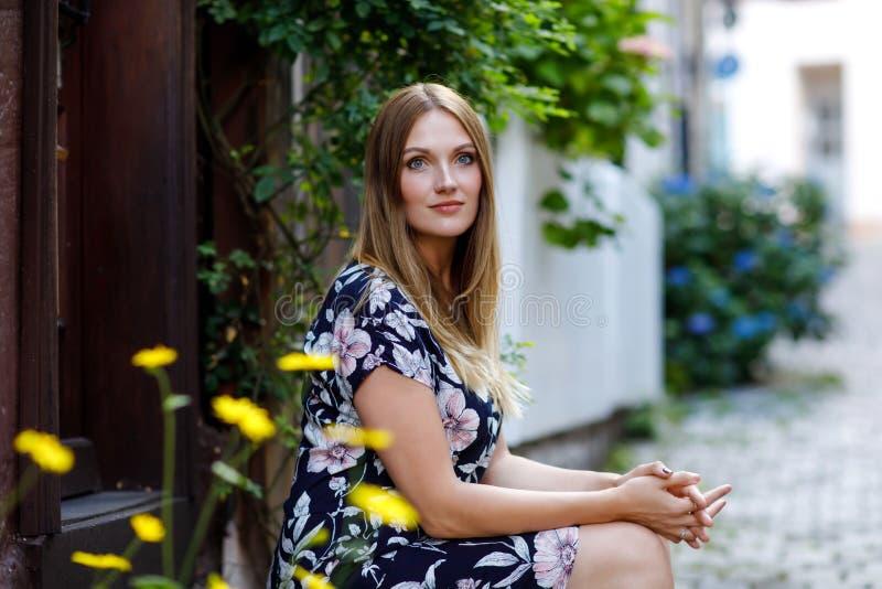 Schöne junge Frau mit den langen Haaren im Sommerkleid, das in der deutschen Stadt spazierengeht Glückliches Mädchen, das herein  stockfotografie