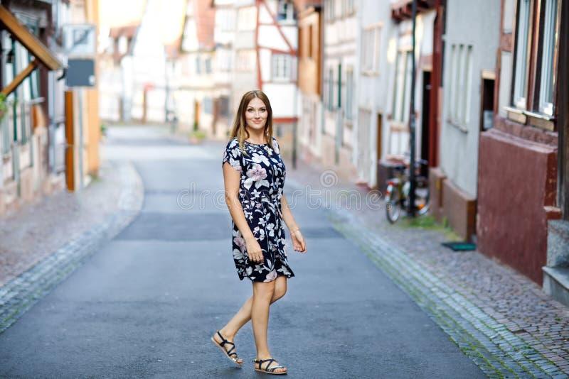 Schöne junge Frau mit den langen Haaren im Sommerkleid, das in der deutschen Stadt spazierengeht Glückliches Mädchen, das herein  lizenzfreies stockbild