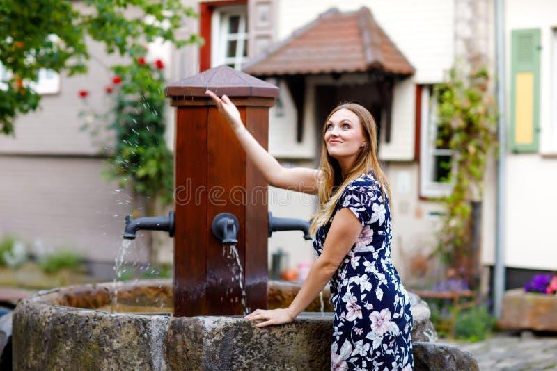Schöne junge Frau mit den langen Haaren im Sommerkleid, das in der deutschen Stadt spazierengeht Glückliches Mädchen, das herein  stockbilder