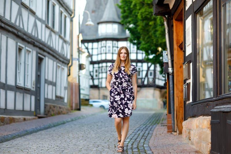 Schöne junge Frau mit den langen Haaren im Sommerkleid, das in der deutschen Stadt spazierengeht Glückliches Mädchen, das herein  lizenzfreie stockbilder
