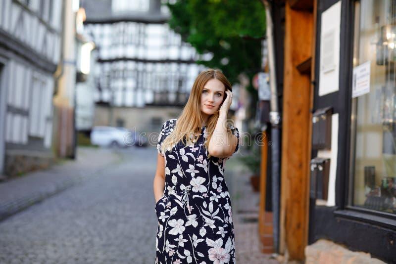 Schöne junge Frau mit den langen Haaren im Sommerkleid, das in der deutschen Stadt spazierengeht Glückliches Mädchen, das herein  lizenzfreie stockfotografie