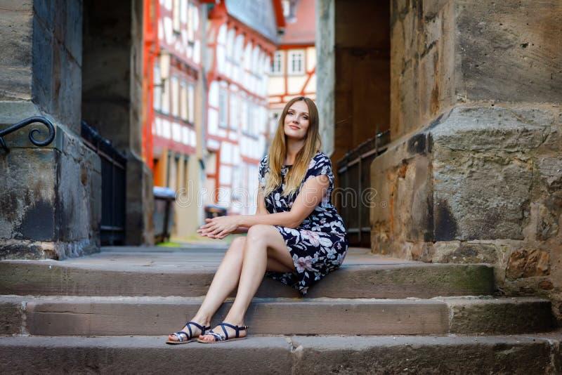 Schöne junge Frau mit den langen Haaren im Sommerkleid, das in der deutschen Stadt spazierengeht Glückliches Mädchen, das herein  stockfotos