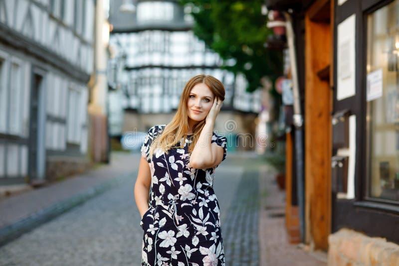 Schöne junge Frau mit den langen Haaren im Sommerkleid, das in der deutschen Stadt spazierengeht Glückliches Mädchen, das herein  lizenzfreie stockfotos