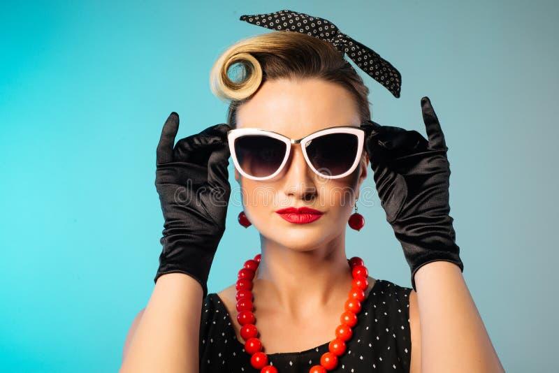 Schöne junge Frau mit den roten Lippen des Zaubers, die Sonnenbrille und fantastische Plastikohrringe tragen lizenzfreies stockbild