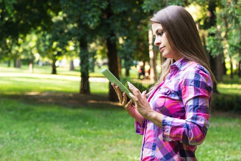 Schöne junge Frau mit digitaler Tablette stockfotografie