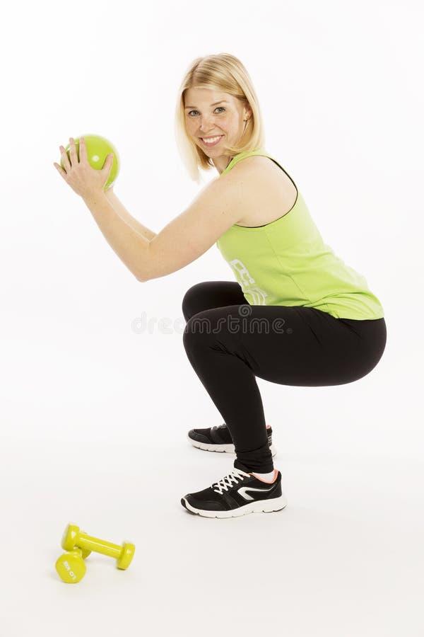 Schöne junge Frau mit einem Ball und Dummköpfen, die Übungen tun lizenzfreie stockfotos