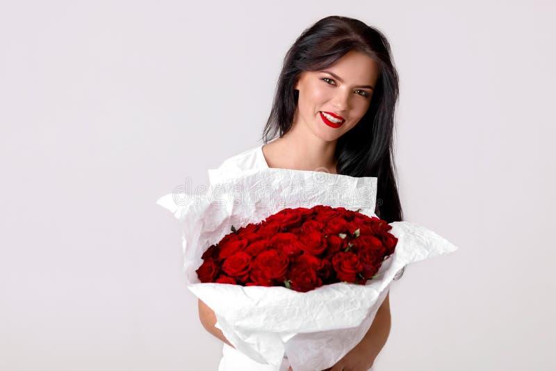 Schöne junge Frau mit einem großen Blumenstrauß von roten Rosen lizenzfreie stockbilder