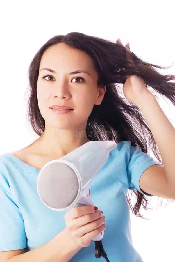 Schöne junge Frau mit einem Haartrockner lizenzfreie stockfotos