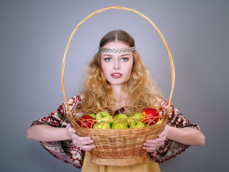 Schöne junge Frau mit einem Korb der Äpfel stockfotos