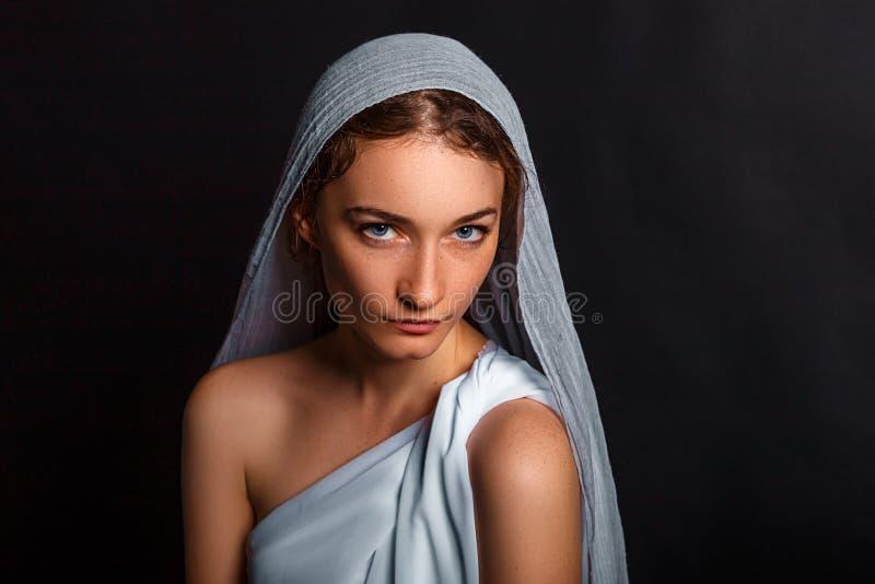 Schöne junge Frau mit einem Schal auf ihrem Kopf und ein Rosenbeet in ihren Händen, bescheidener Blick, glaubende Frau stockfotos