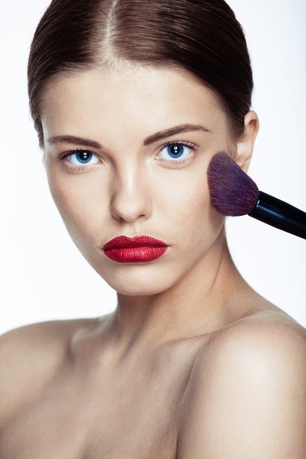 Schöne junge Frau mit einer Make-upbürste. lizenzfreie stockfotografie