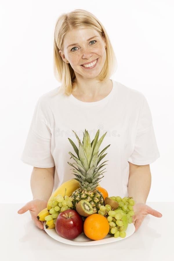 Schöne junge Frau mit einer Schüssel des Fruchtmischungslächelns stockbilder