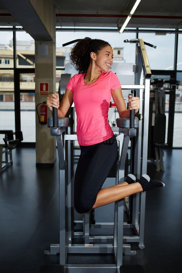 Schöne junge Frau mit einer schlanken Zahl ihre Bauchmuskeln ausübend lizenzfreie stockbilder
