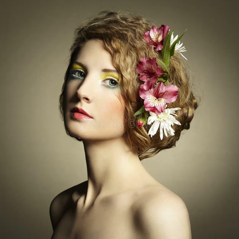 Schöne junge Frau mit empfindlichen Blumen in ihrem Haar stockfotos
