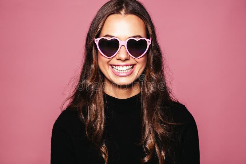 Schöne junge Frau mit geformter Sonnenbrille des Herzens stockbild
