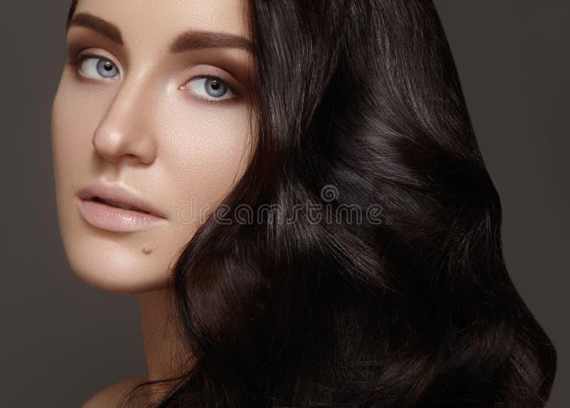 Schöne junge Frau mit gelockter Frisur des Volumens Schönheit Brunettemodell mit sauberer Haut, Zaubermodemake-up stockfotografie