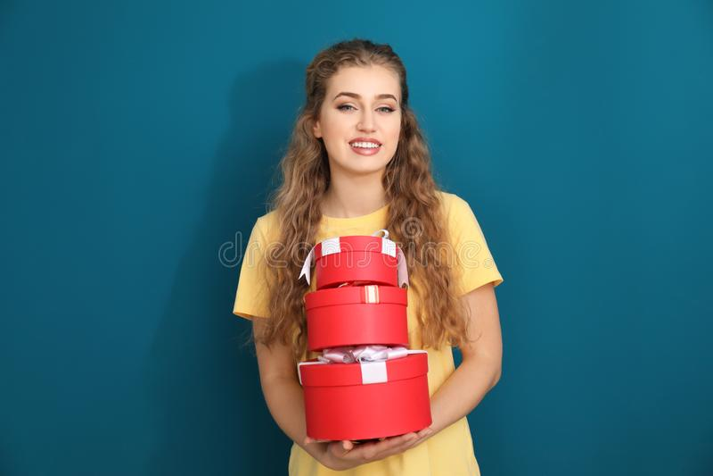 Schöne junge Frau mit Geschenkboxen auf Farbhintergrund stockfotos