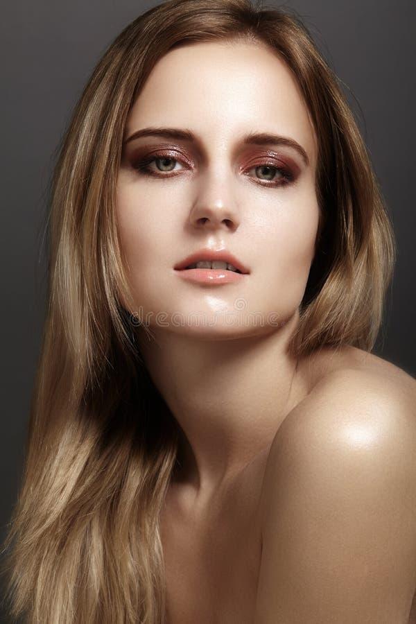 Schöne junge Frau mit Glanzaugen- und -lippenantlitz Saubere Haut der Schönheit, Modemake-up Kosmetik, bilden, Frisur stockfotografie