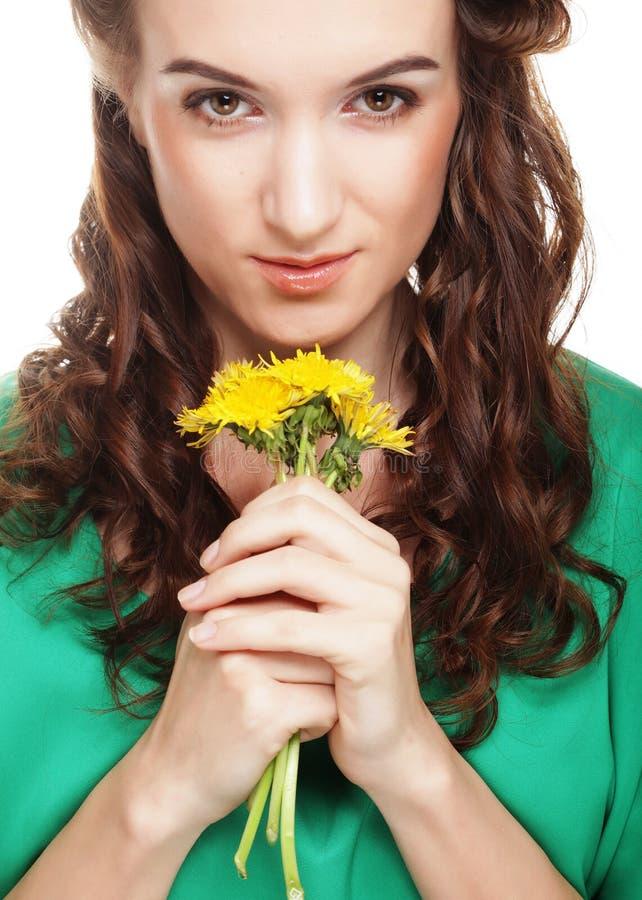 Schöne junge Frau mit großem gelbem Löwenzahn lizenzfreies stockbild
