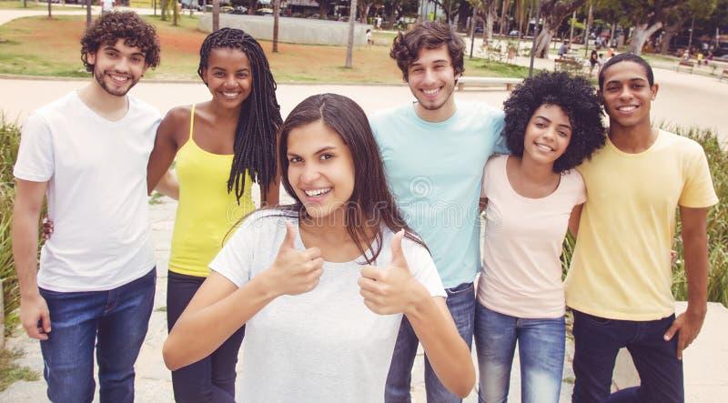 Schöne junge Frau mit Gruppe Freunden im Retro- Blick stockbilder