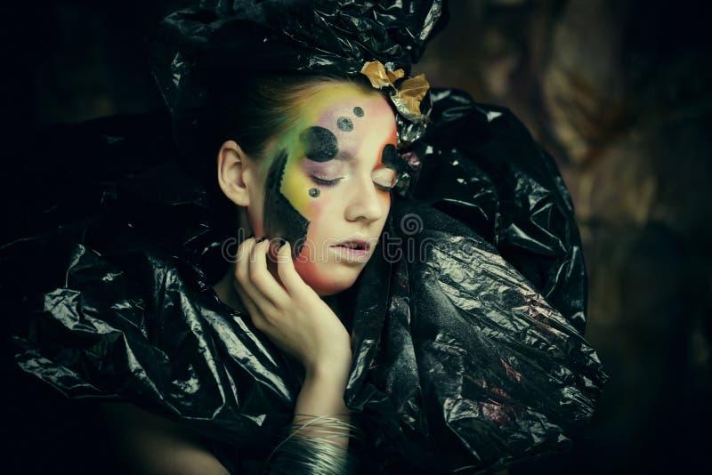 Schöne junge Frau mit hellem Fantasiemake-up und Kostüm, das auf einem schwarzen Hintergrund in den Rauchwolken aufwirft Hallowee lizenzfreies stockbild