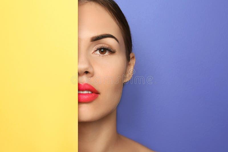 Schöne junge Frau mit hellem Lippenstift und leerem Plakat auf Farbhintergrund lizenzfreies stockbild