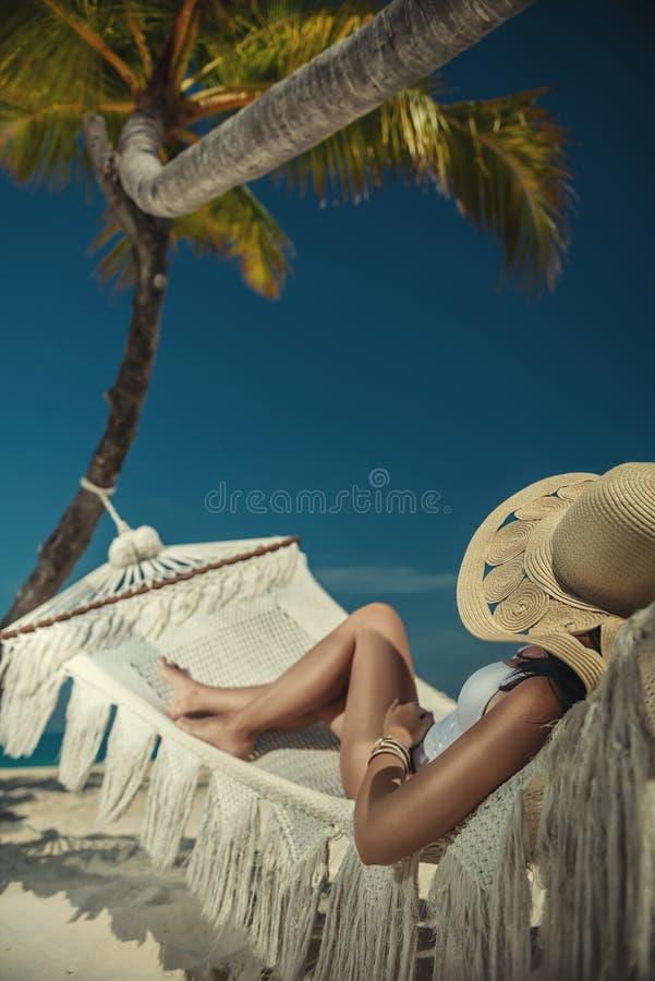 Schöne junge Frau mit Hut auf weißem Strand, schöne Landschaft mit Frau in Malediven, tropisches Paradies stockfotografie
