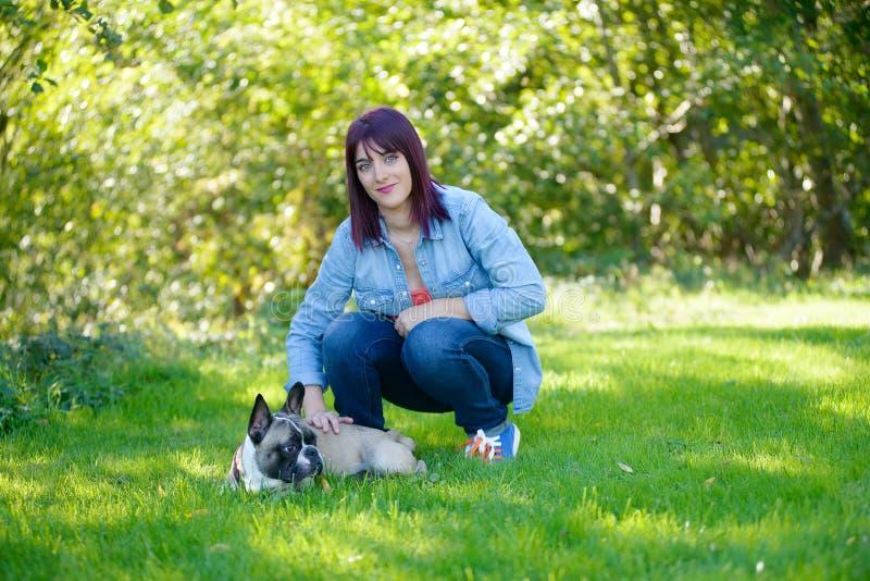 Schöne junge Frau mit ihrer Hundefranzösischen Bulldogge lizenzfreie stockfotos