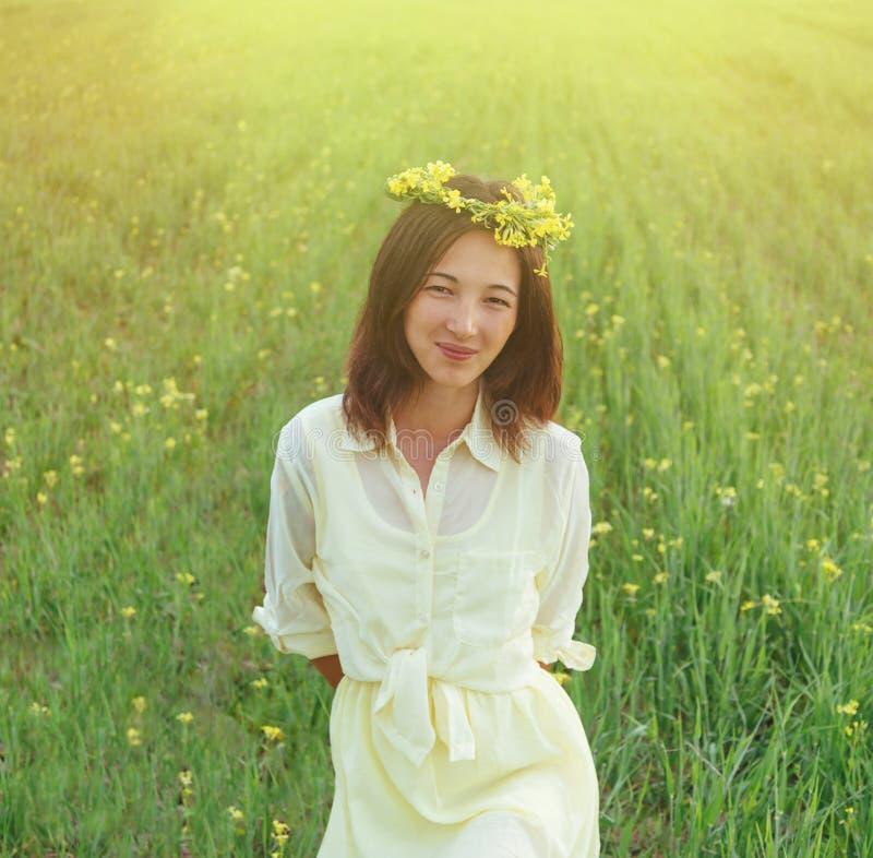 Schöne junge Frau mit Kranz von Blumen im Sommer lizenzfreies stockbild