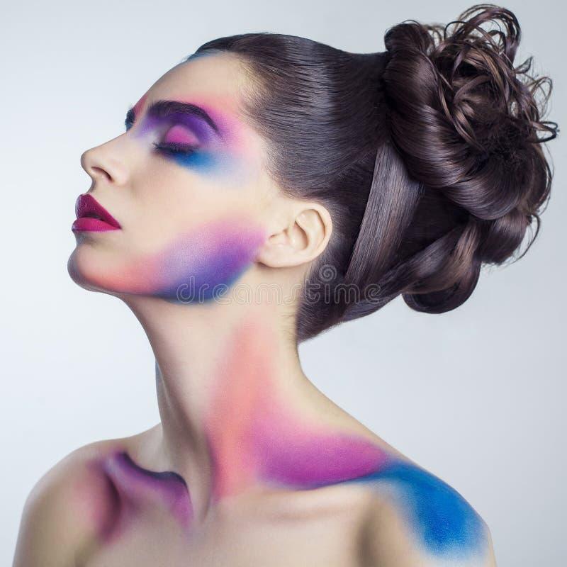 Schöne junge Frau mit kreativem farbigem Make-up und gelockte gesammelte Frisur und gemalter farbiger Körper stockfotos