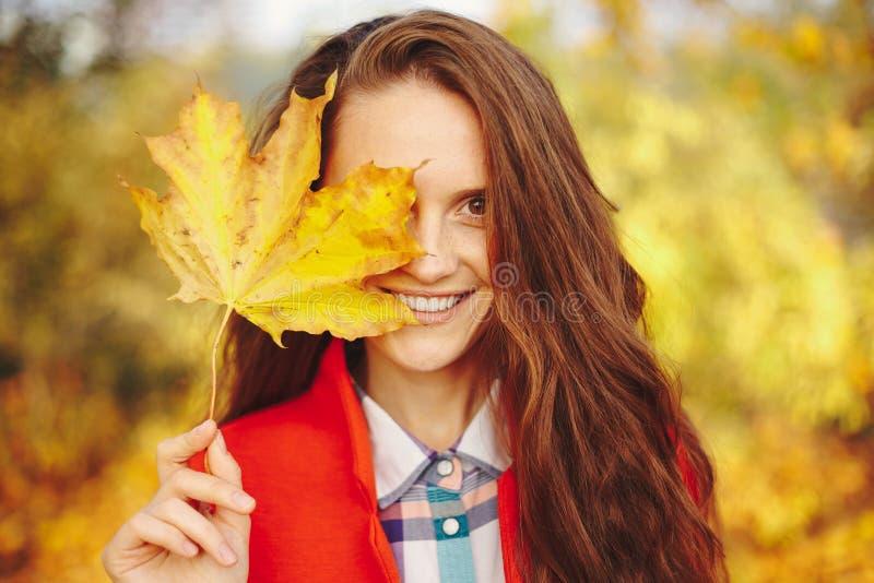 Schöne junge Frau mit langem Bedeckungsgesicht des gewellten Haares mit einem L stockfotos