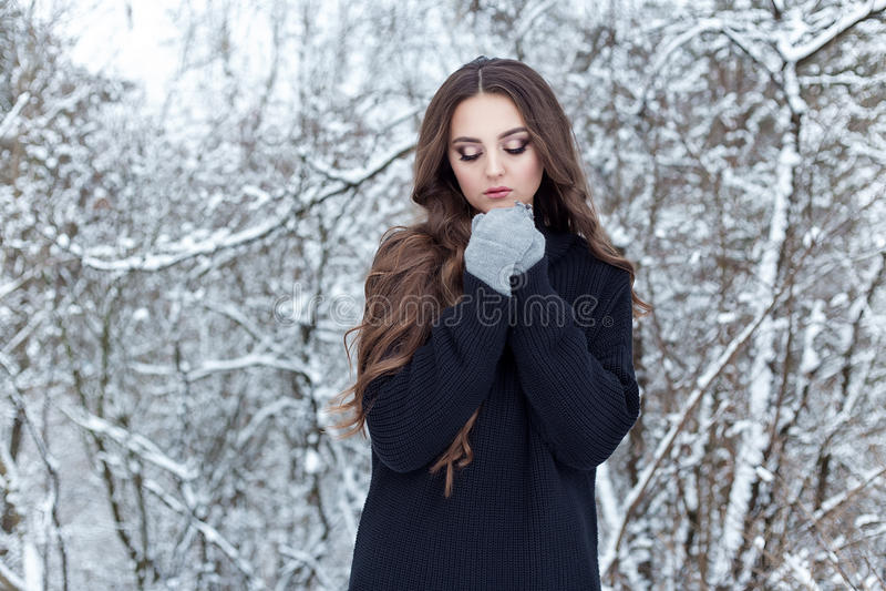 Schöne junge Frau mit langem traurigem einsamem Weg des dunklen Haares im Winterholz in einer schwarzen Jacke und in den Handschu stockbilder