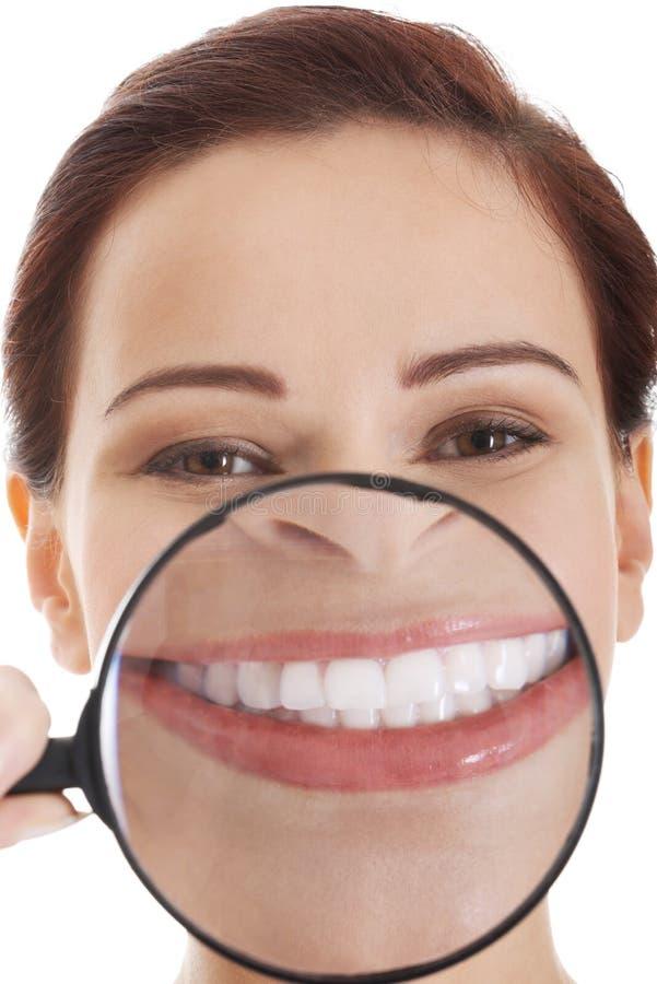 Schöne junge Frau mit Lupe auf Mund. lizenzfreie stockbilder
