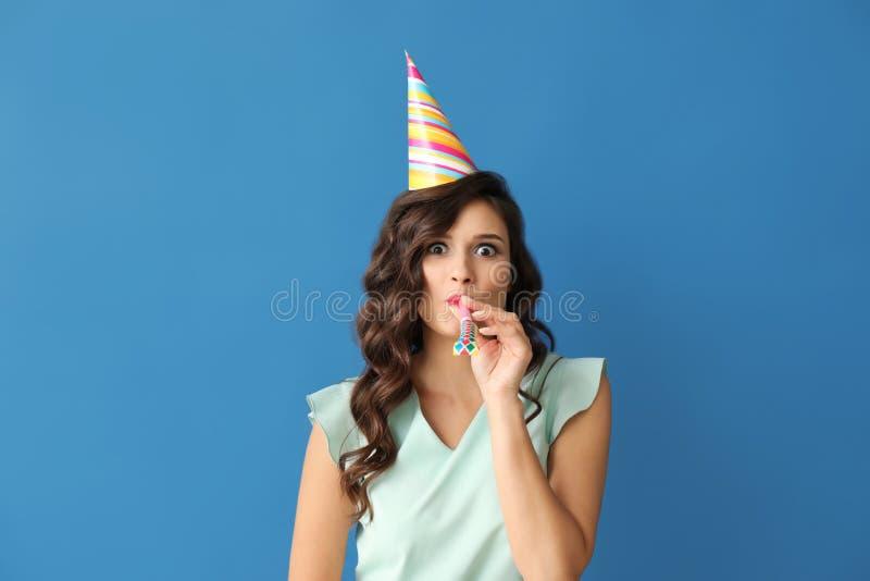 Schöne junge Frau mit Parteipfeife und -kappe auf Farbhintergrund lizenzfreie stockbilder