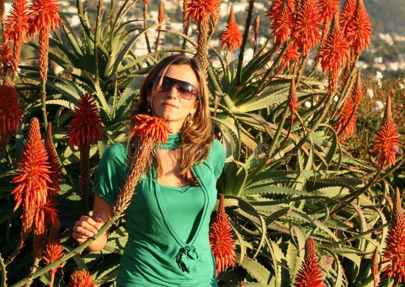 Schöne junge Frau mit roten Blumen lizenzfreies stockbild