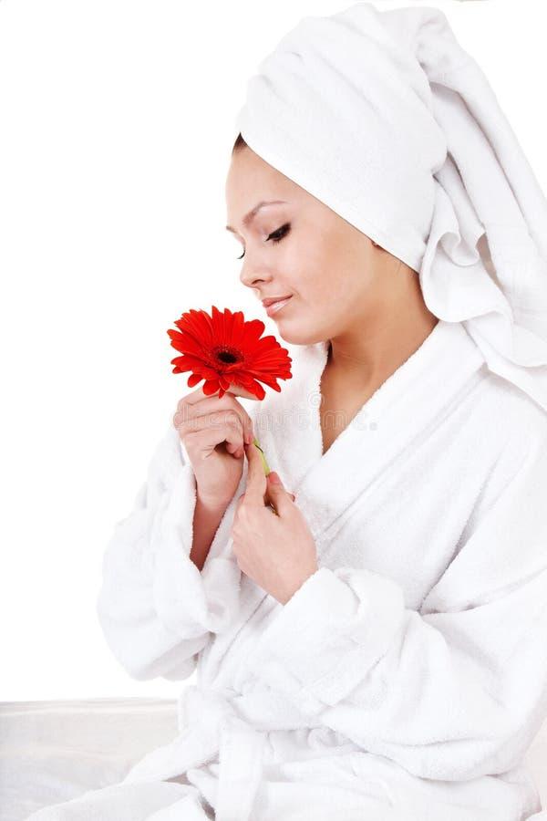Schöne junge Frau mit roter Blume im Badekurort. stockbild