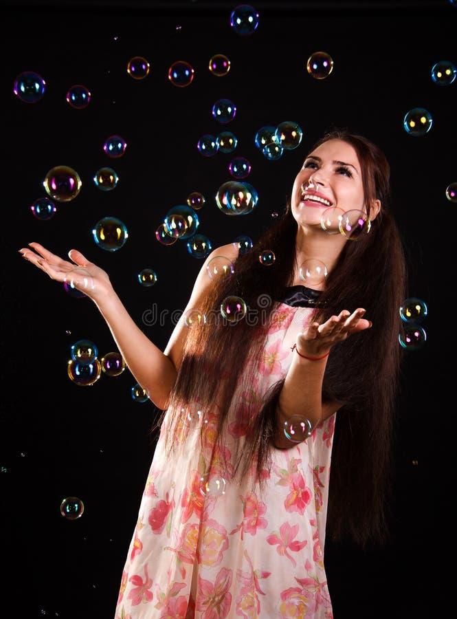 Schöne junge Frau mit Seifenblasen stockbilder