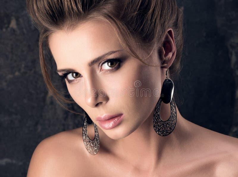 Schöne junge Frau mit sinnlichem Blick Berufsmake-up, Frisur und große Ohrringe stockfotos