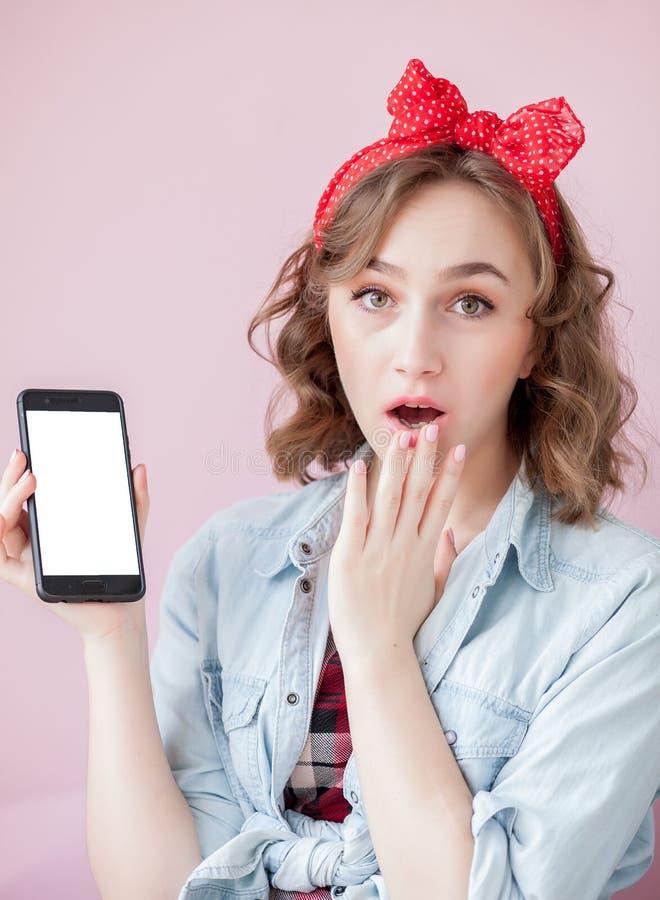 Schöne junge Frau mit Stift-obenmake-up und -frisur über rosa Hintergrund mit Handy mit Kopienraum stockbilder