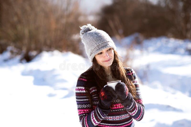 Schöne junge Frau mit Tasse Kaffee in der Winternatur stockfotos