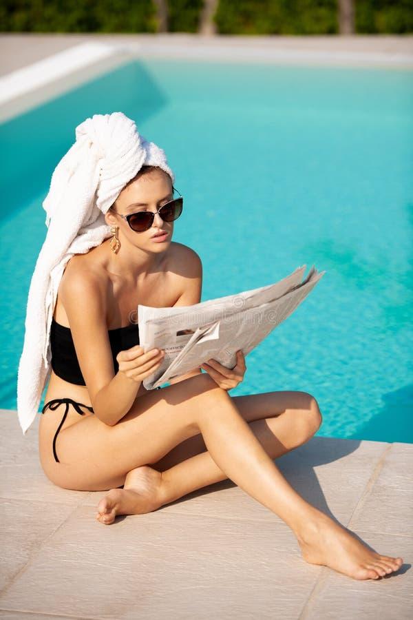 Schöne junge Frau mit Tuch auf ihrer Haarlesezeitung nahe Hotelpool stockfoto
