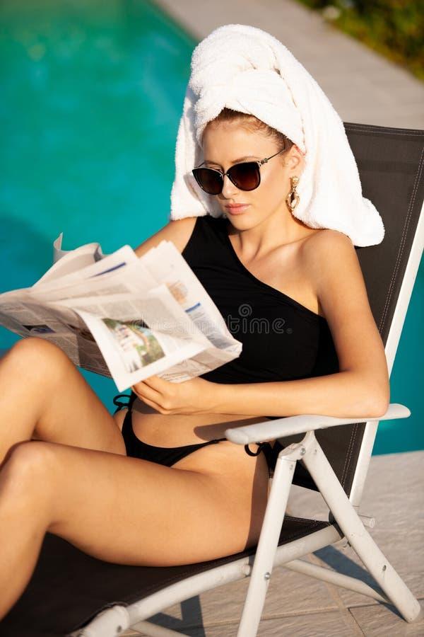 Schöne junge Frau mit Tuch auf ihrer Haarlesezeitung nahe Hotelpool stockfotos
