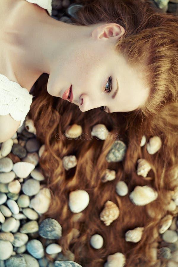 Schöne junge Frau mit ungewöhnlicher Frisur auf Strand lizenzfreie stockfotografie