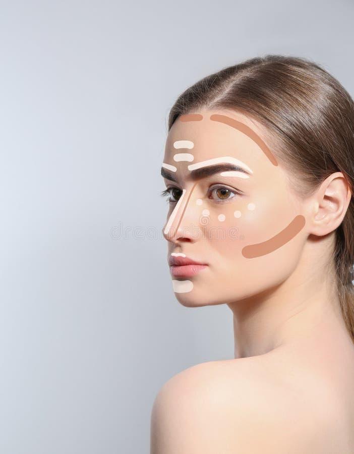 Schöne junge Frau mit verschiedenen Farbgrundlagen auf Gesicht gegen grauen Hintergrund, Raum für Text lizenzfreie stockbilder