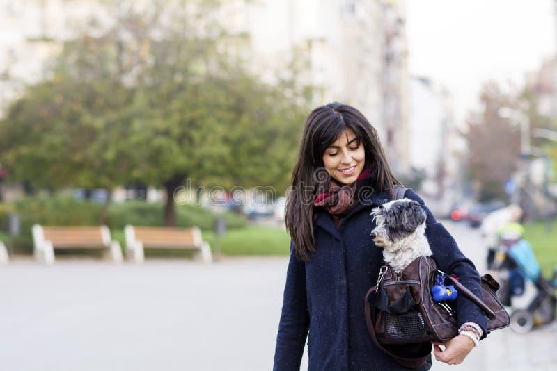 Schöne junge Frau mit weißem Hund in der Tragetasche lizenzfreie stockfotos