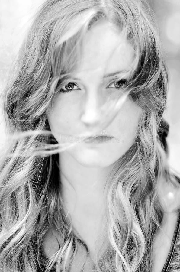 Schöne junge Frau mit Wind im gewellten Haar lizenzfreie stockfotografie